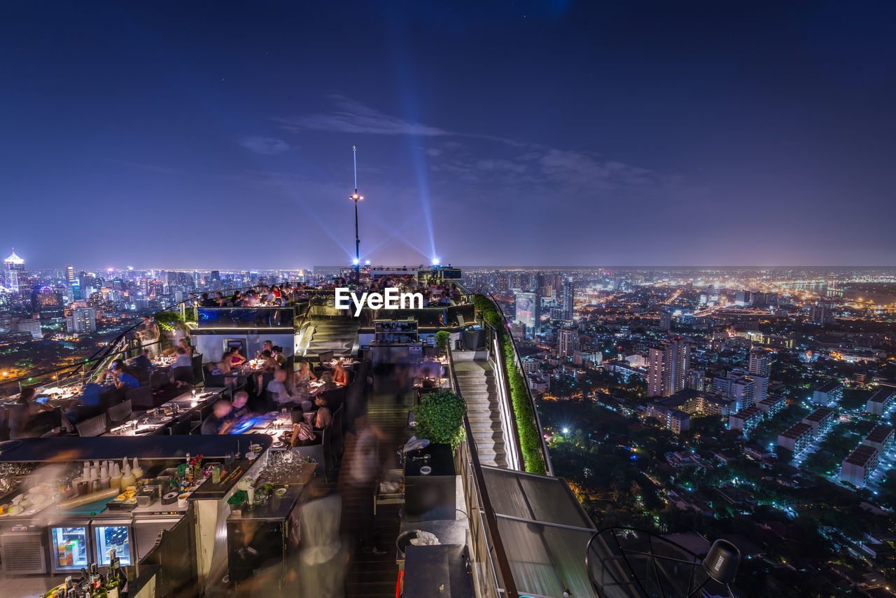 city, architecture, building exterior, built structure, illuminated, night, sky, cityscape, crowd, crowded, high angle view, building, transportation, nature, street, road, outdoors, city life, residential district, office building exterior, skyscraper
