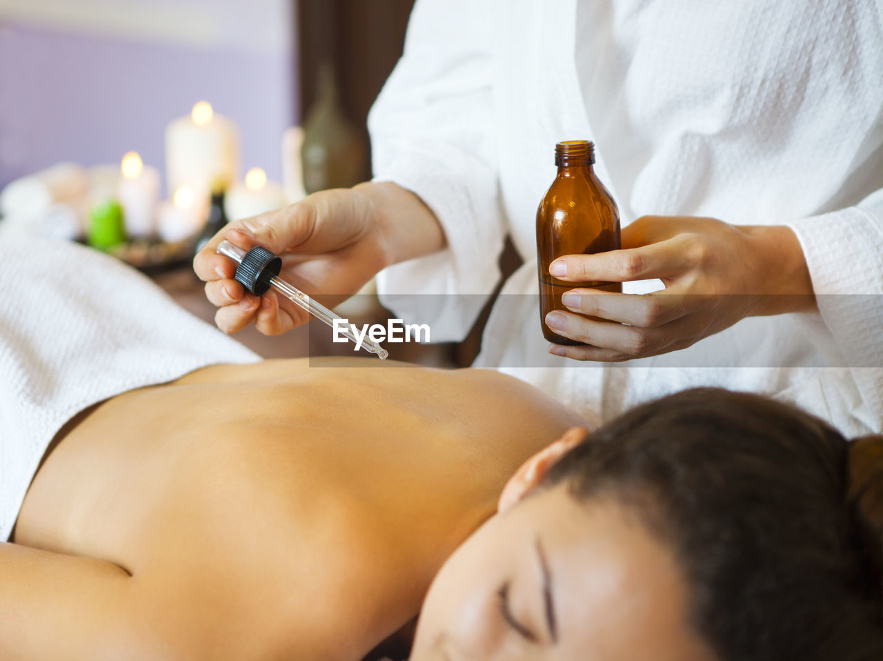 Midsection of woman holding oil bottle at spa
