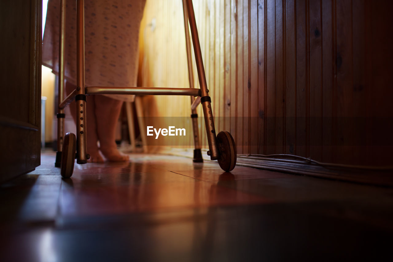 Low Section Of Woman Walking With Mobility Walker At Home