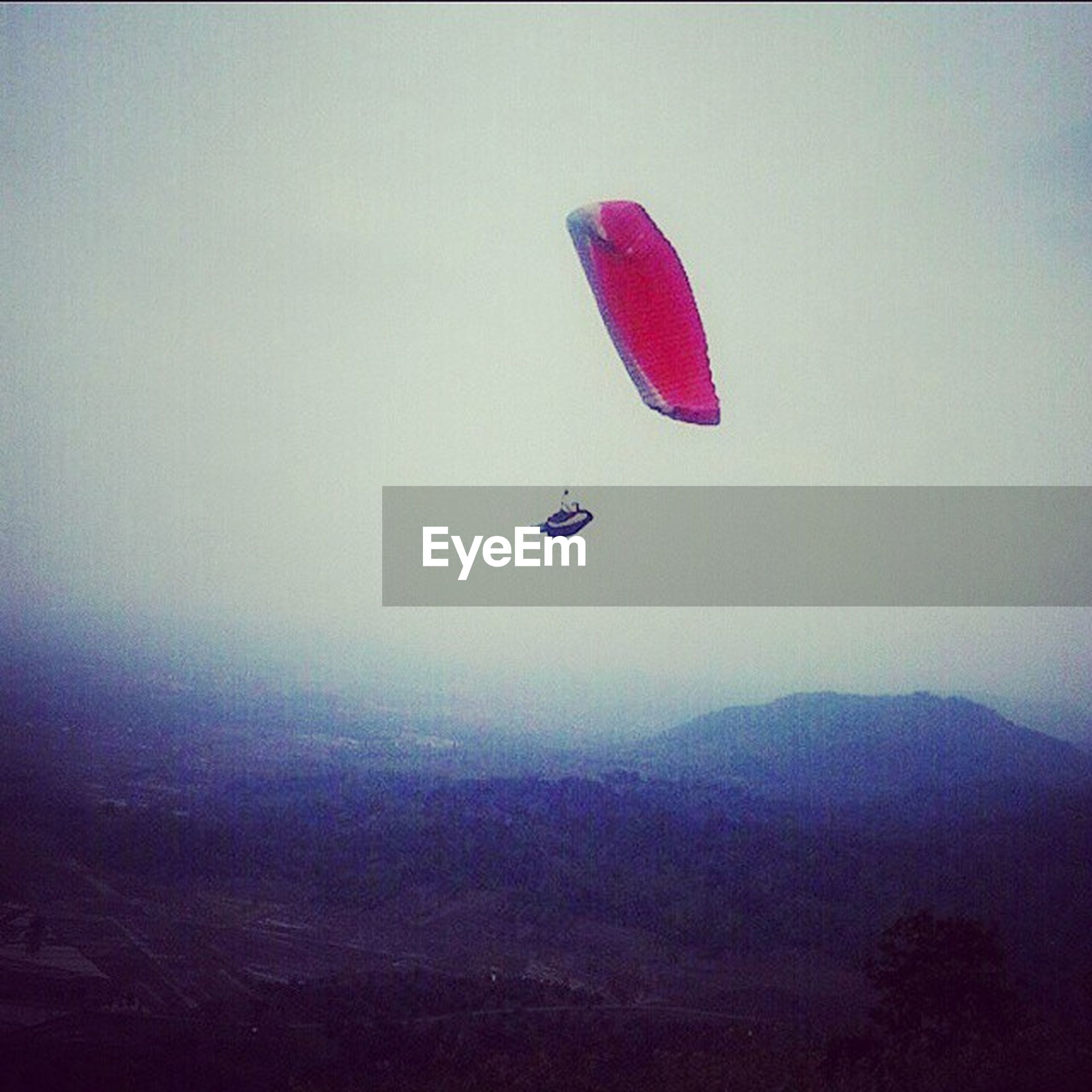 flying, mid-air, adventure, transportation, copy space, scenics, mountain, tranquil scene, tranquility, beauty in nature, parachute, extreme sports, nature, landscape, paragliding, unrecognizable person, fog, sky, travel