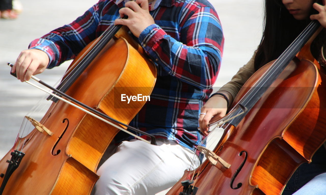 Midsection of people playing violin in city
