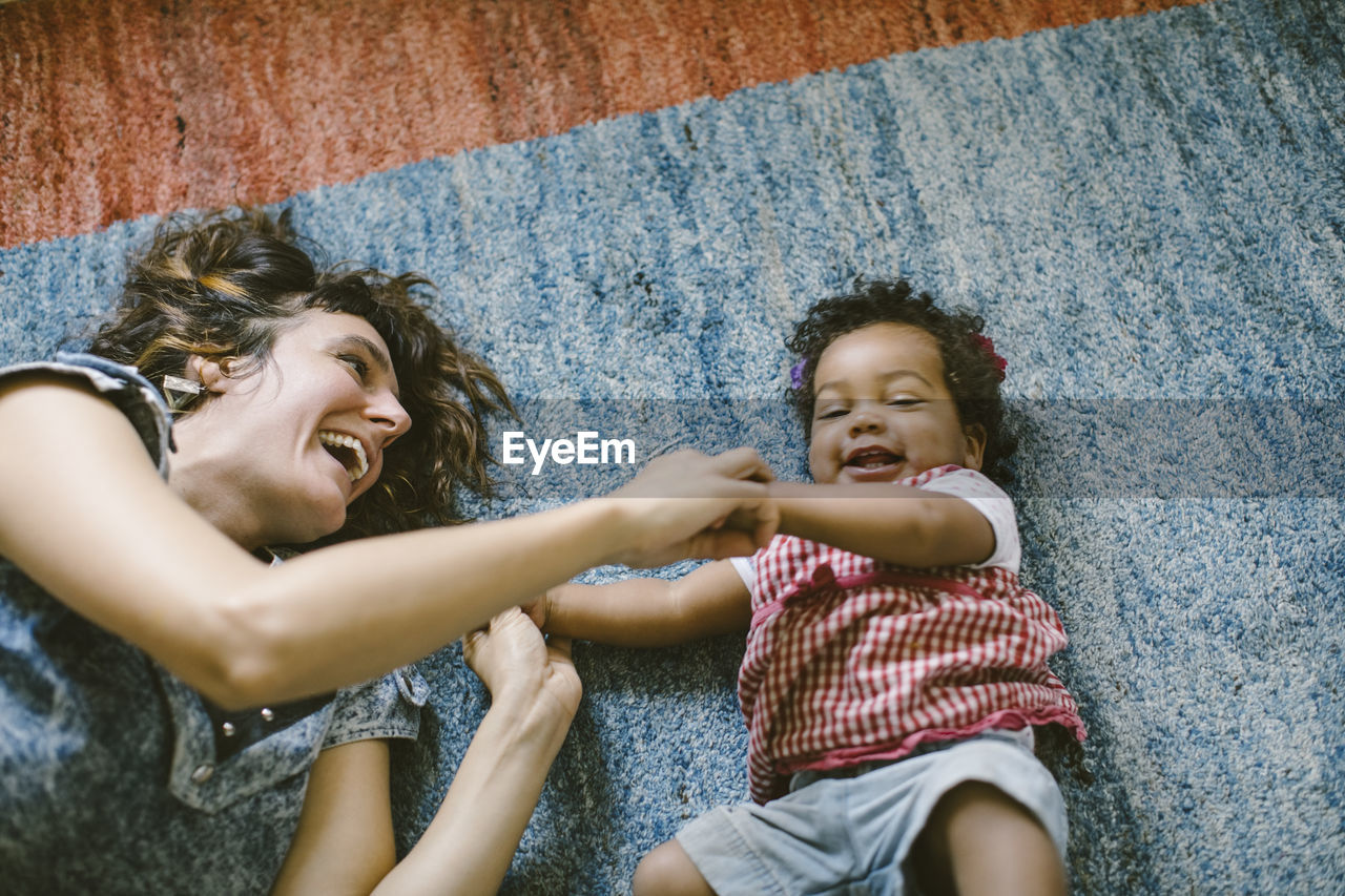 High angle view of happy mother and daughter lying on carpet at home