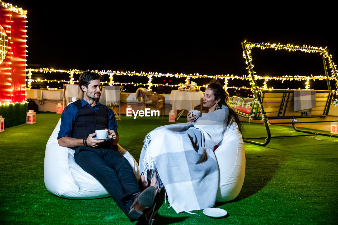 Young Couple Having Coffee While Relaxing On Illuminated Terrace At Night