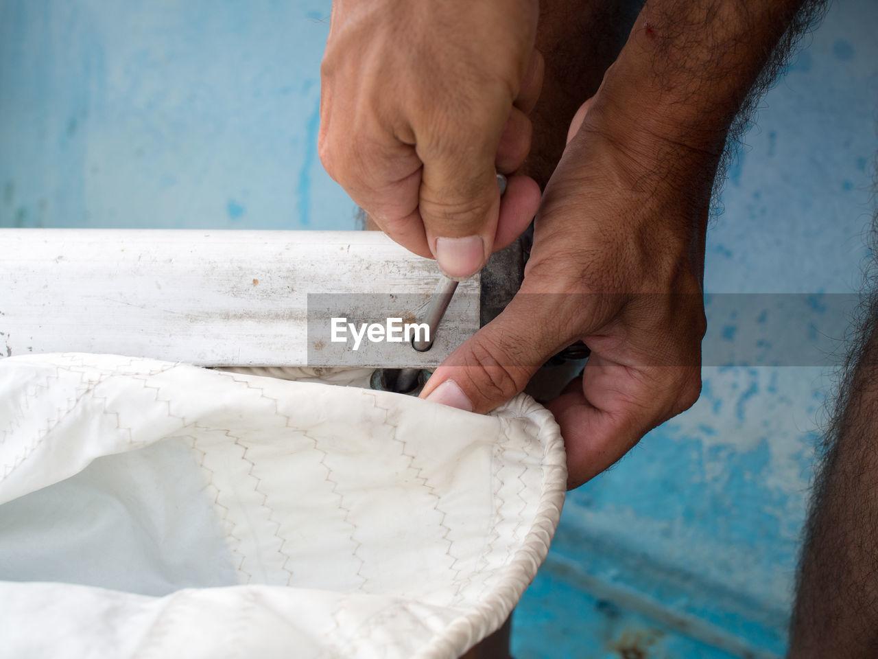 Close-Up Of Hands Fixing Sail