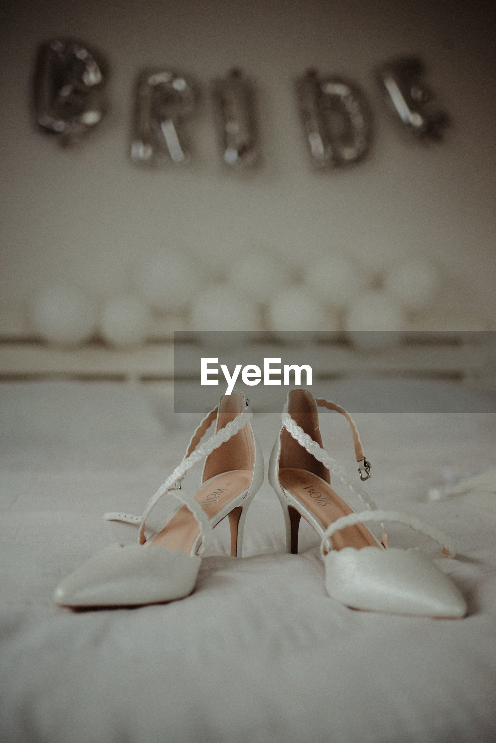 Close-up of high heels on bed
