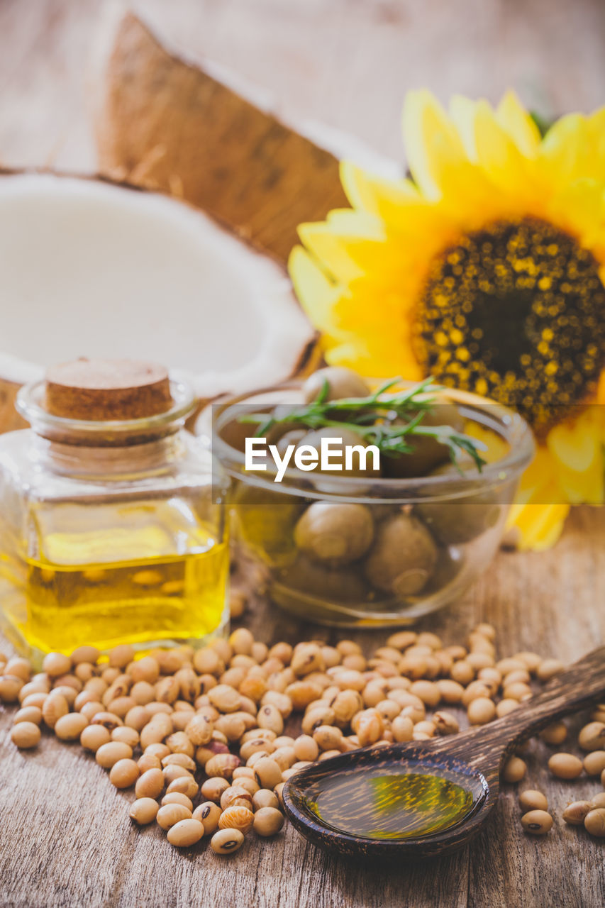 food and drink, food, freshness, bowl, table, still life, no people, oil, container, close-up, plant, glass - material, ingredient, indoors, wood - material, transparent, spice, wellbeing, yellow, cooking oil, herb, olive oil