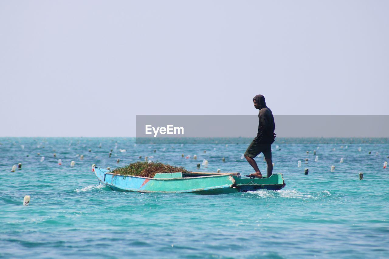 Man on sea against clear sky