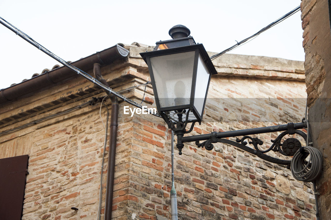 lighting equipment, low angle view, architecture, street light, building exterior, street, built structure, sky, wall, electricity, technology, wall - building feature, no people, day, brick wall, electric lamp, brick, building, outdoors, clear sky, light, electrical equipment