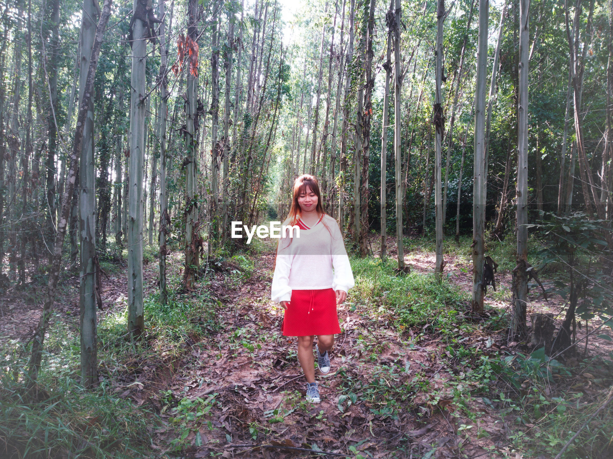 Full length of mid adult woman walking on field amidst trees in forest