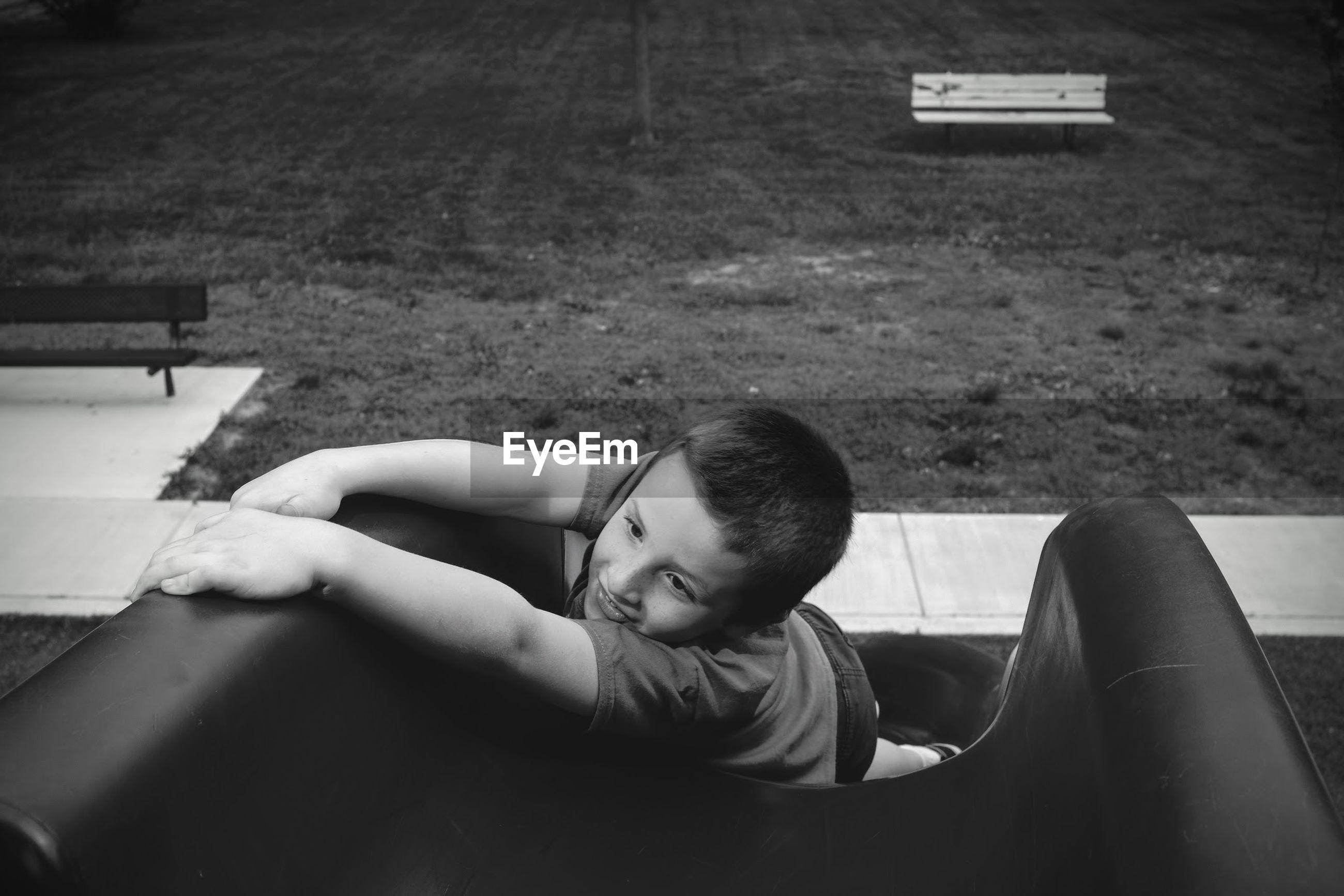 High angle view of boy enjoying slide at playground
