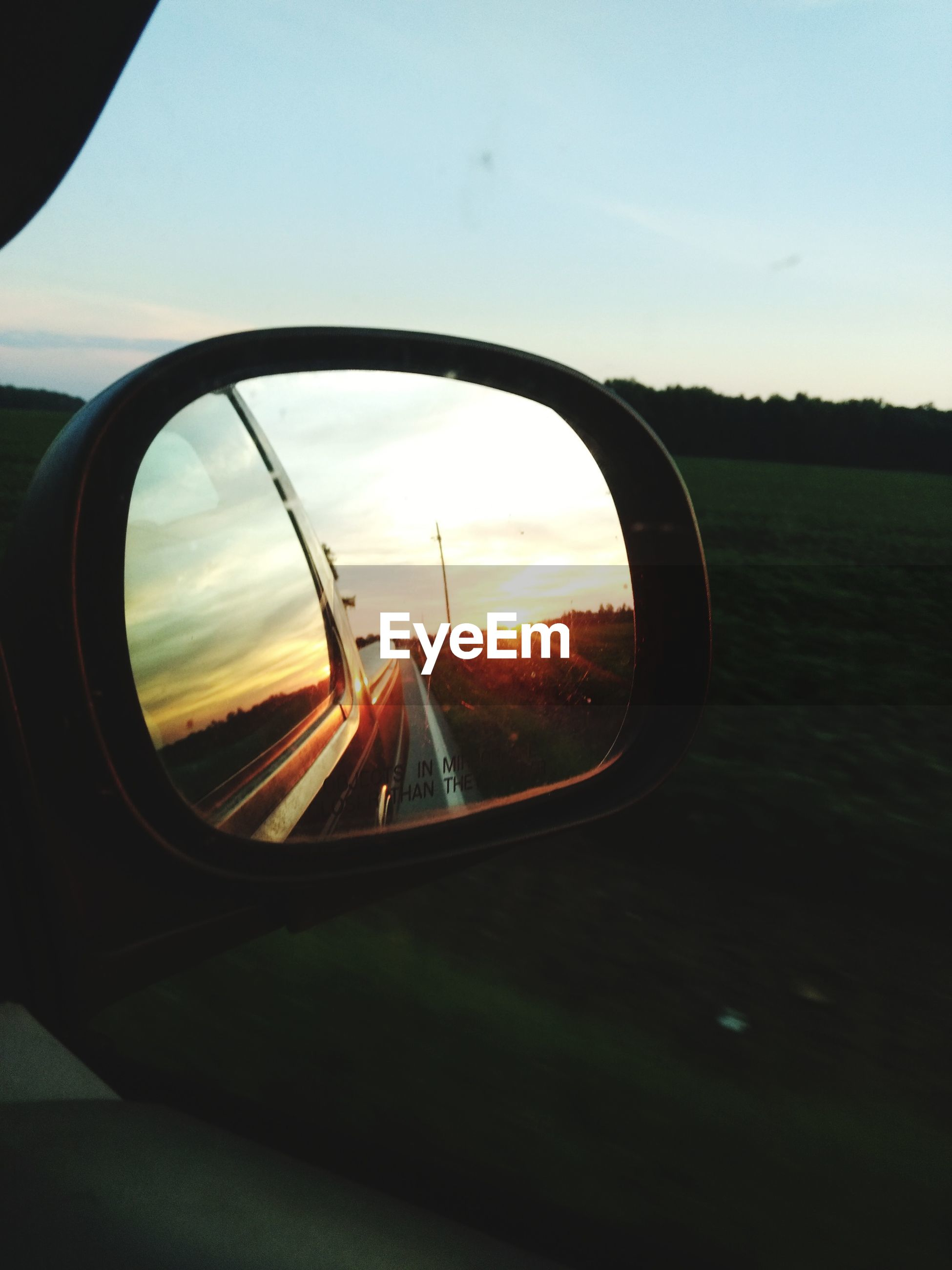 CLOSE-UP OF SIDE-VIEW MIRROR AGAINST SUNSET