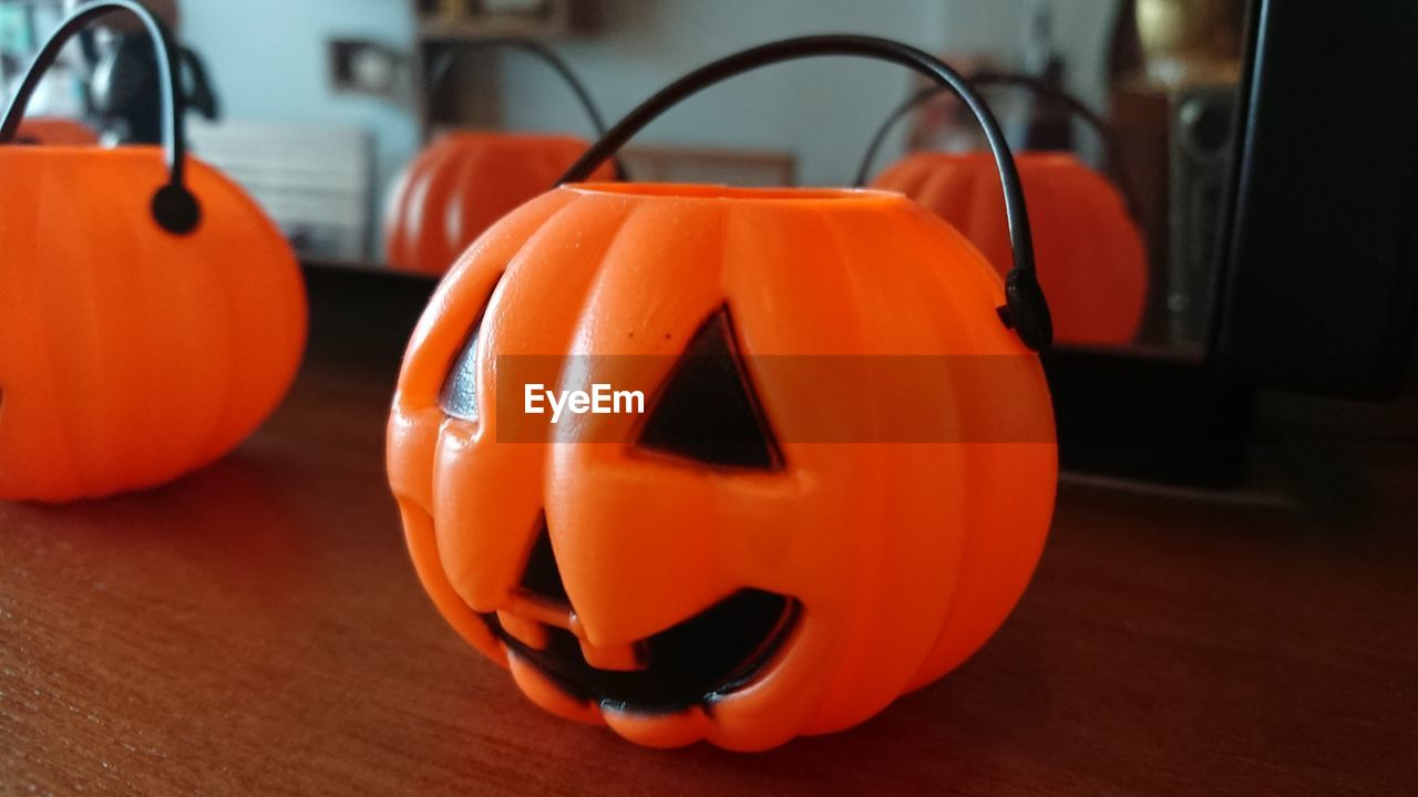 orange color, halloween, food and drink, food, pumpkin, table, indoors, celebration, focus on foreground, anthropomorphic face, no people, face, anthropomorphic, jack o' lantern, close-up, still life, creativity, art and craft, vegetable