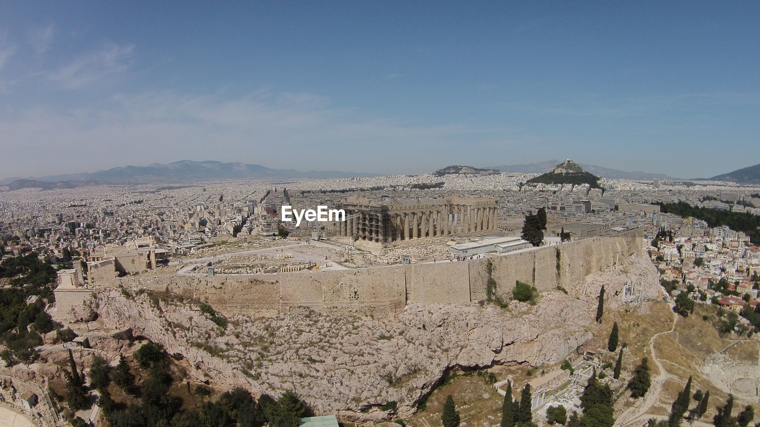 Parthenon on acropolis by residential district against sky