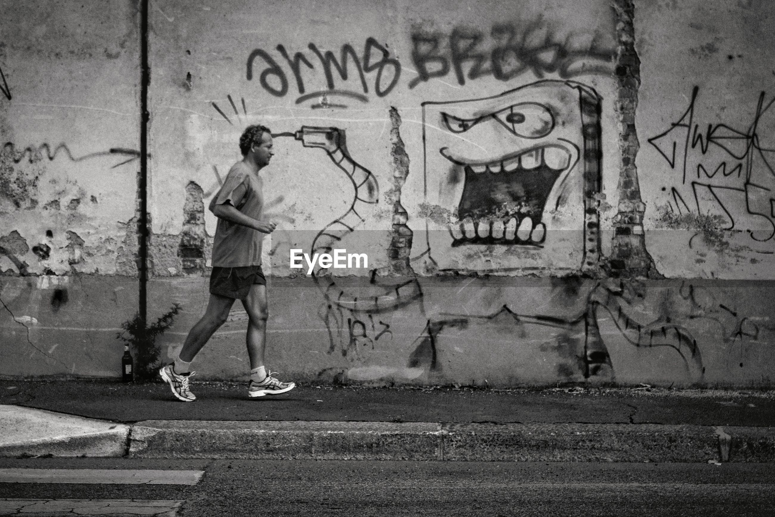 FULL LENGTH OF MAN WITH SKATEBOARD ON STREET