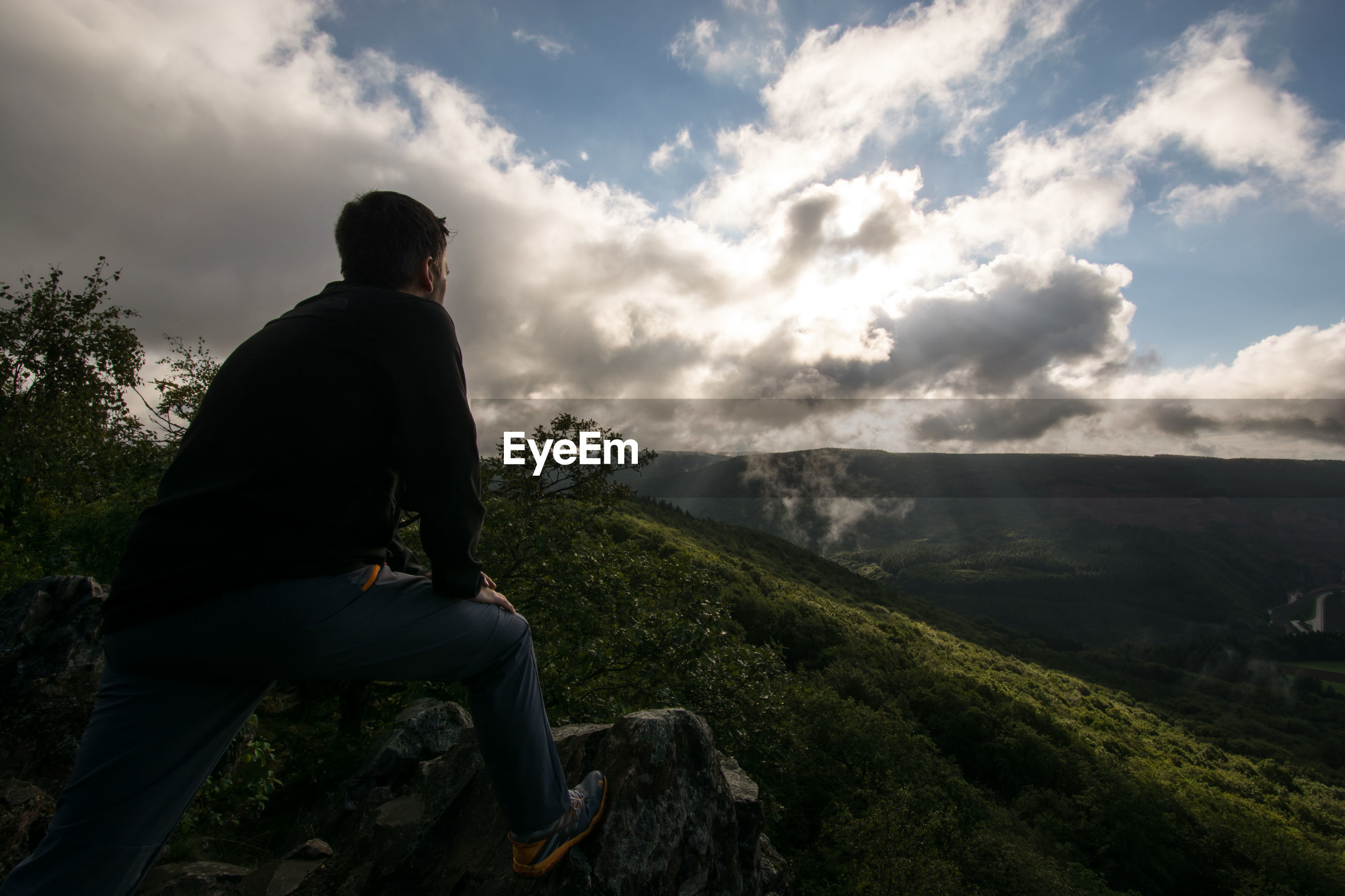 Side view of man standing on cliff against landscape
