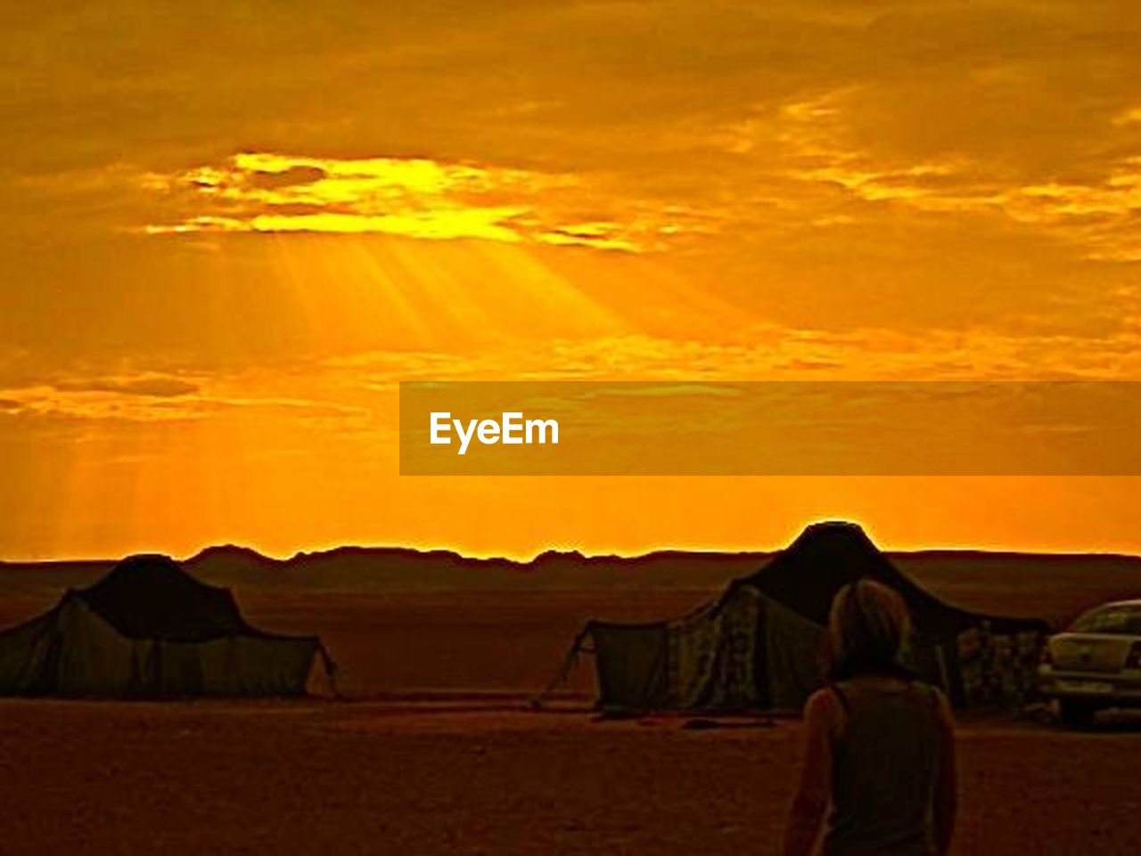 sunset, desert, sky, heat - temperature, outdoors, cloud - sky, silhouette, sunlight, scenics, nature, built structure, arid climate, building exterior, architecture, beauty in nature, adult, people, day