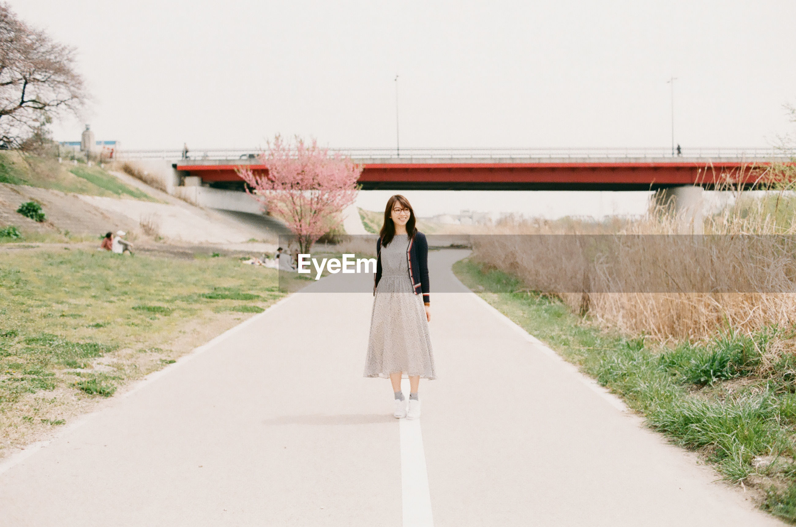 Full length of woman standing on street by bridge against clear sky