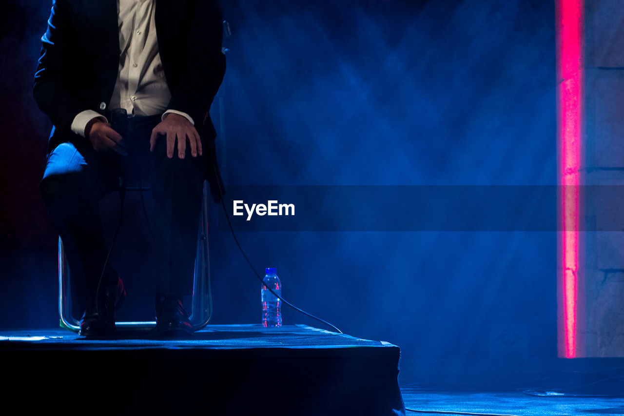 one person, blue, real people, midsection, standing, men, business, occupation, arts culture and entertainment, front view, indoors, low section, business person, lifestyles, illuminated, stage, music, water, stage - performance space