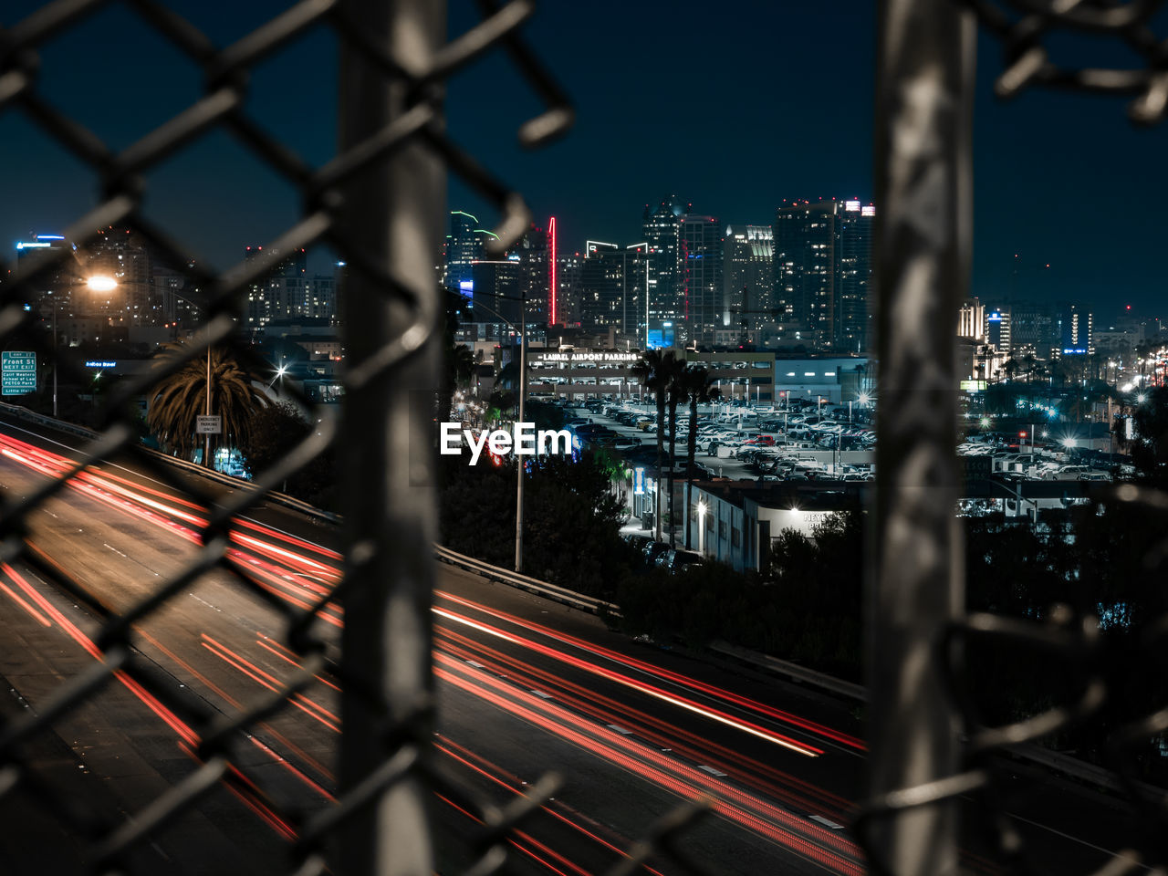 High Angle View Of Light Trails On Road In City Seen Through Broken Chainlink Fence At Night