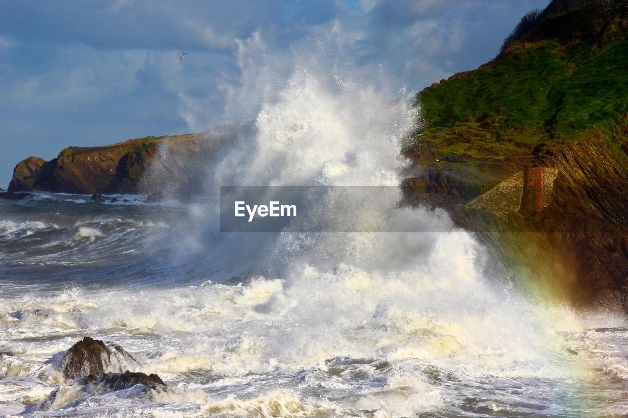 VIEW OF WAVES SPLASHING ON SEA AGAINST SKY