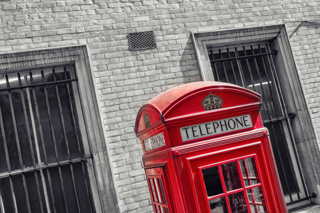Close-Up Of Red Telephone Booth Against Building In City