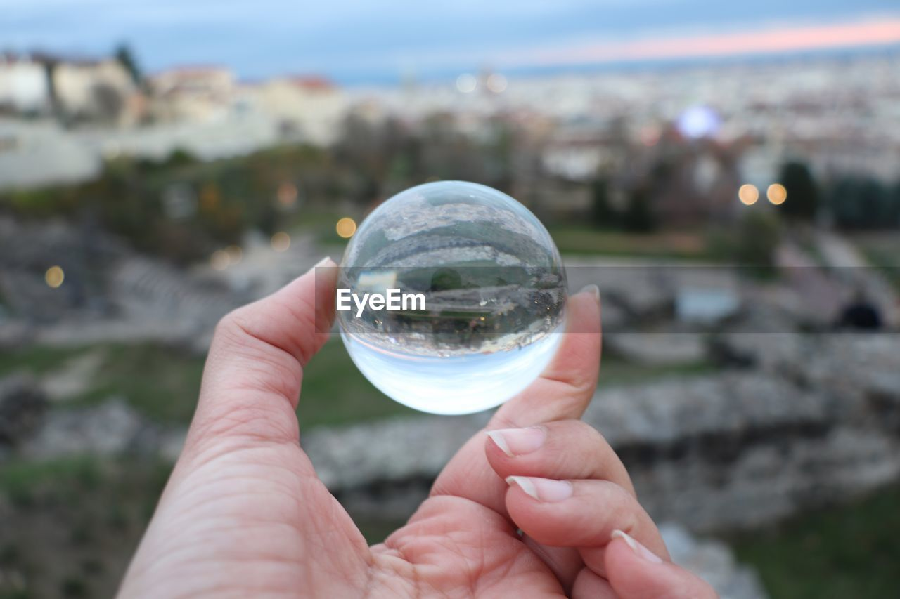 Cropped Hand Holding Crystal Ball Against City