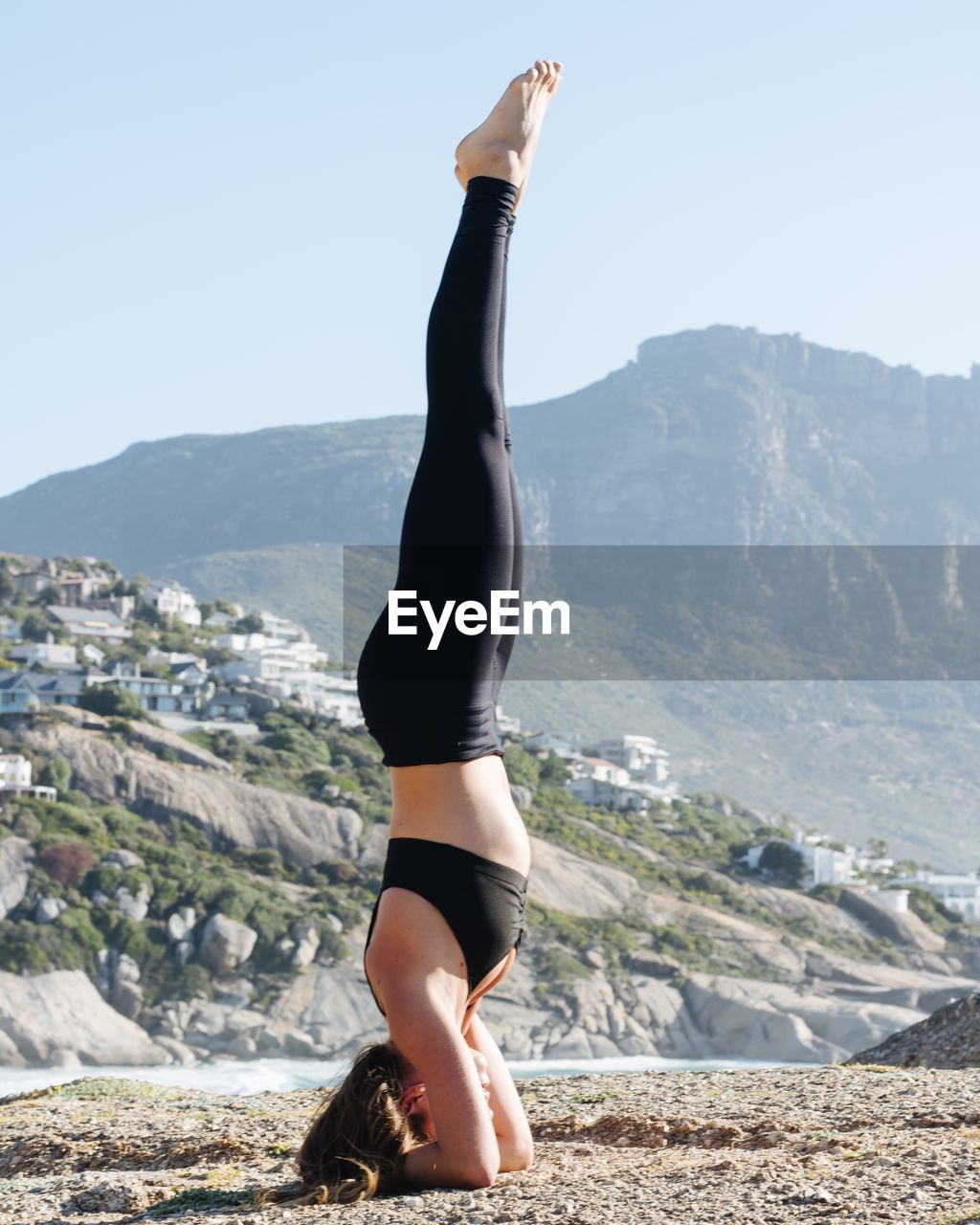 Woman practicing yoga on mountain against clear sky