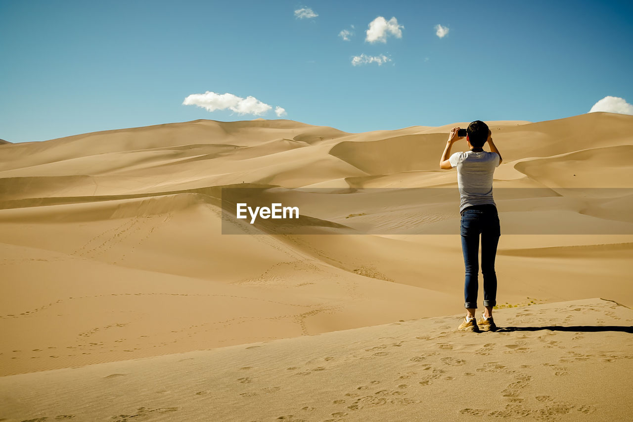 Rear View Of Woman Photographing Sand Dunes In Desert