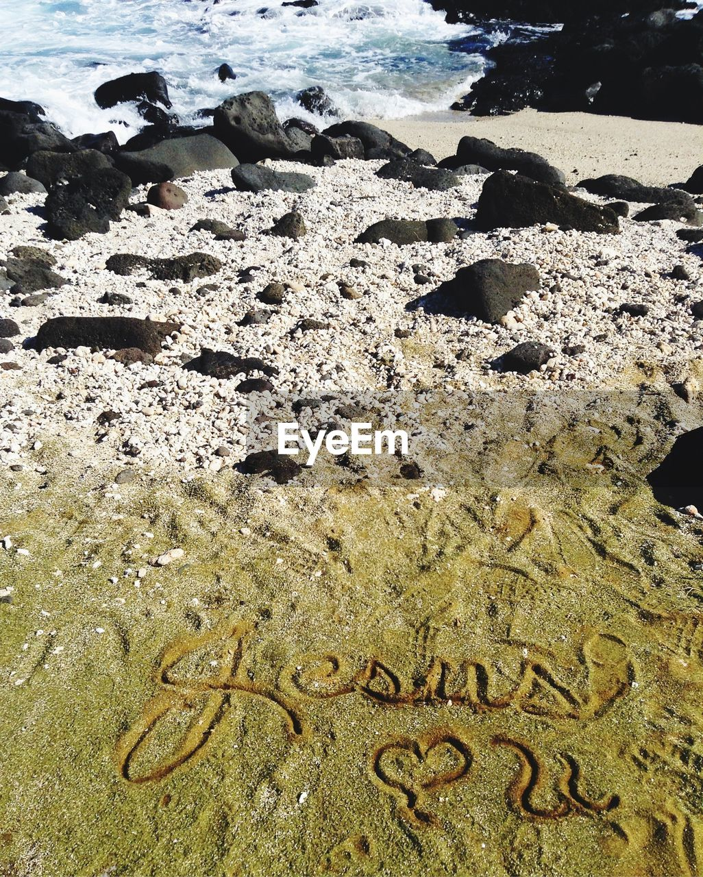 High angle view of text on sand at beach during sunny day
