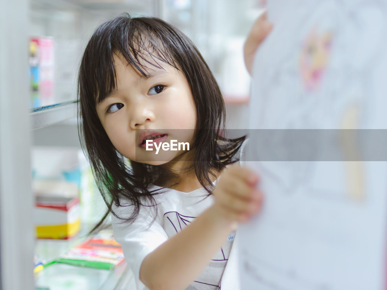 Close-Up Of Girl Looking At Drawing In Home