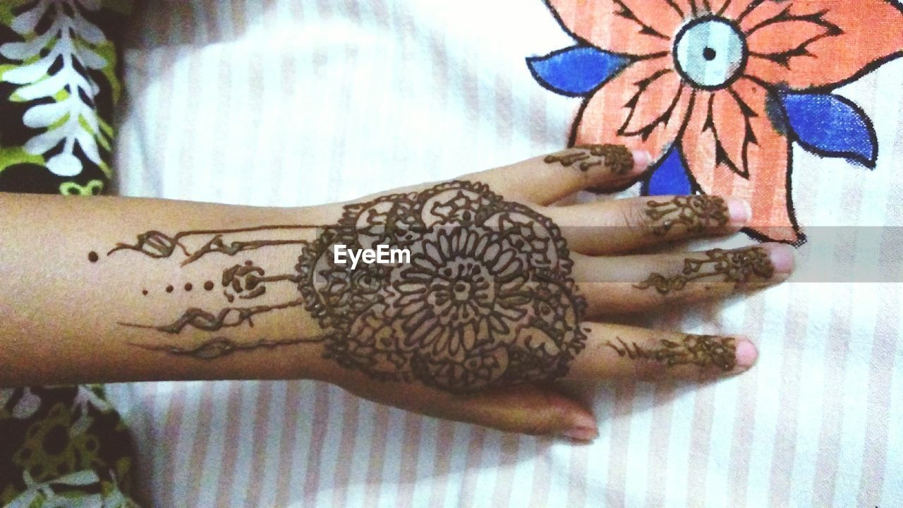 tattoo, one person, human hand, creativity, hand, human body part, real people, art and craft, indoors, pattern, lifestyles, women, adult, henna tattoo, high angle view, design, representation, leisure activity, floral pattern, body part, human limb, finger, human arm