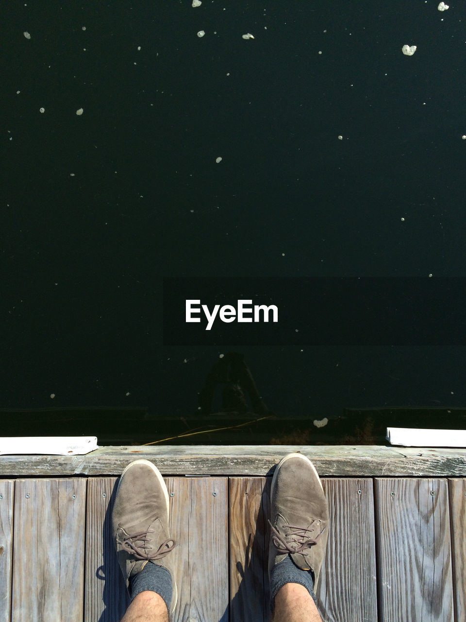 Low Section Of Person Standing On Wooden Pier