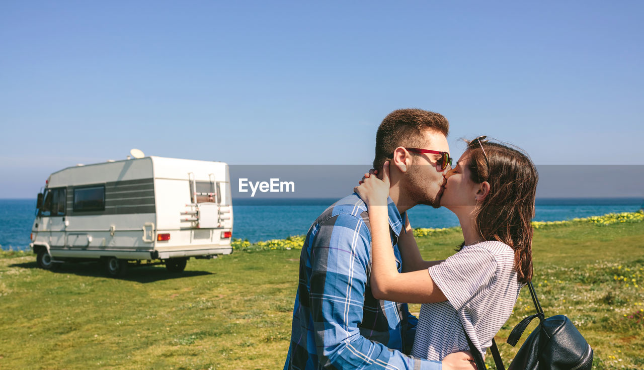 Side View Of Couple Kissing On Shore Against Clear Blue Sky