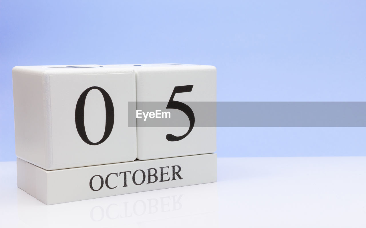 text, communication, western script, blue, copy space, indoors, no people, studio shot, still life, white color, number, close-up, capital letter, blue background, calendar, white background, wall - building feature, table, black color, celebration