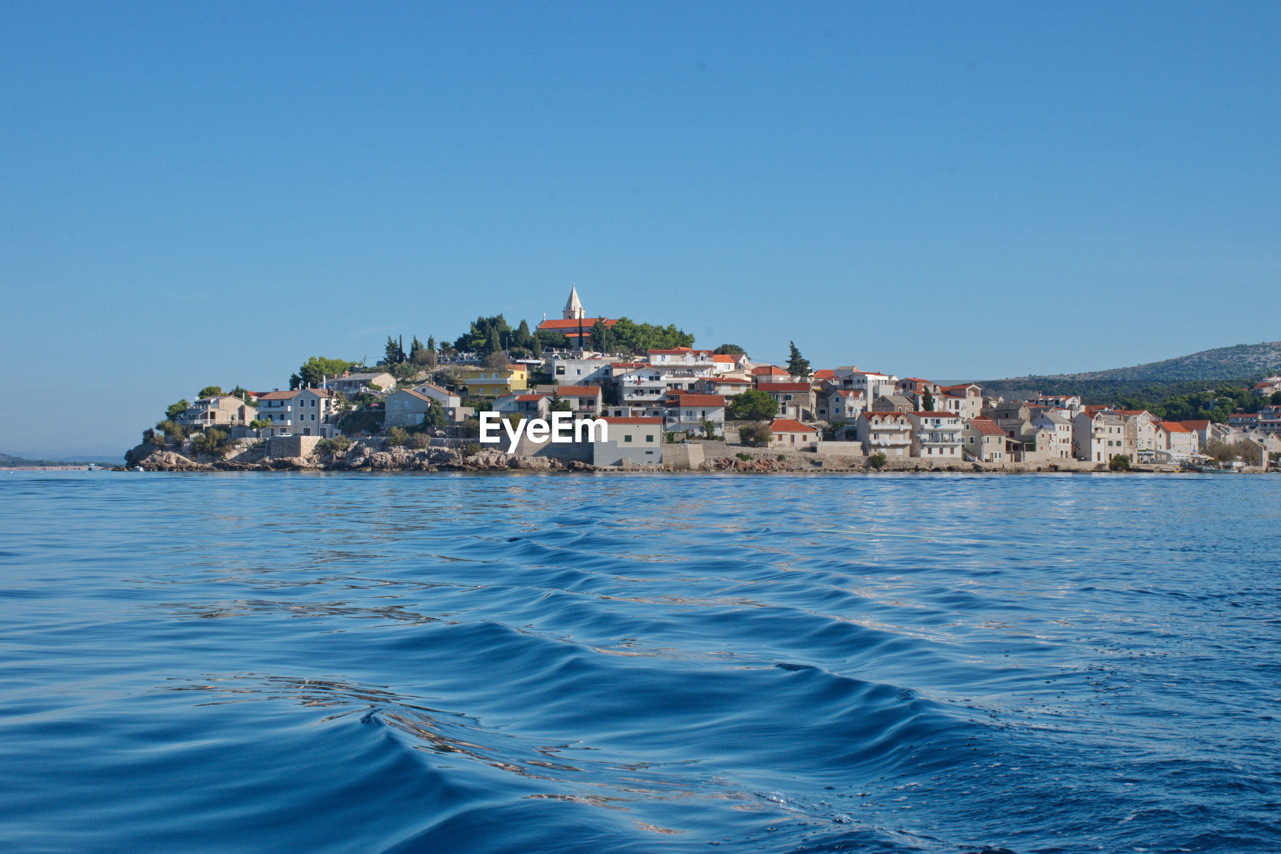 Sailing on motor boat on adriatic sea with primosten cityscape in the background.