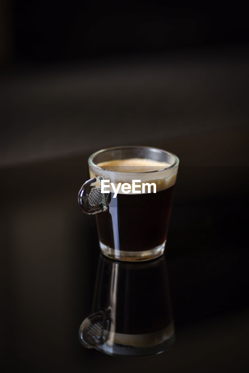 CLOSE-UP OF COFFEE CUP ON GLASS