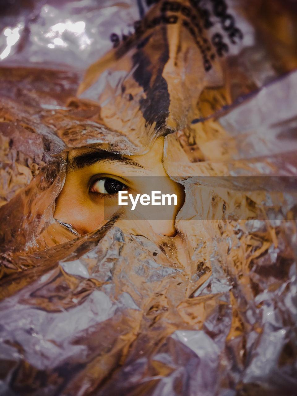 Close-up of human eye seen through foil