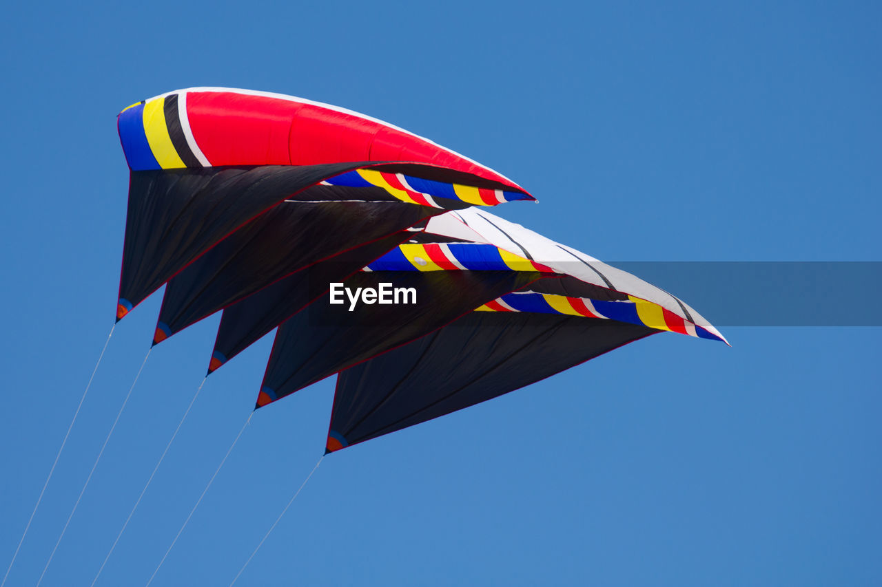 low angle view, clear sky, multi colored, blue, flying, wind, no people, day, outdoors, parachute, childhood, sky, nature, close-up