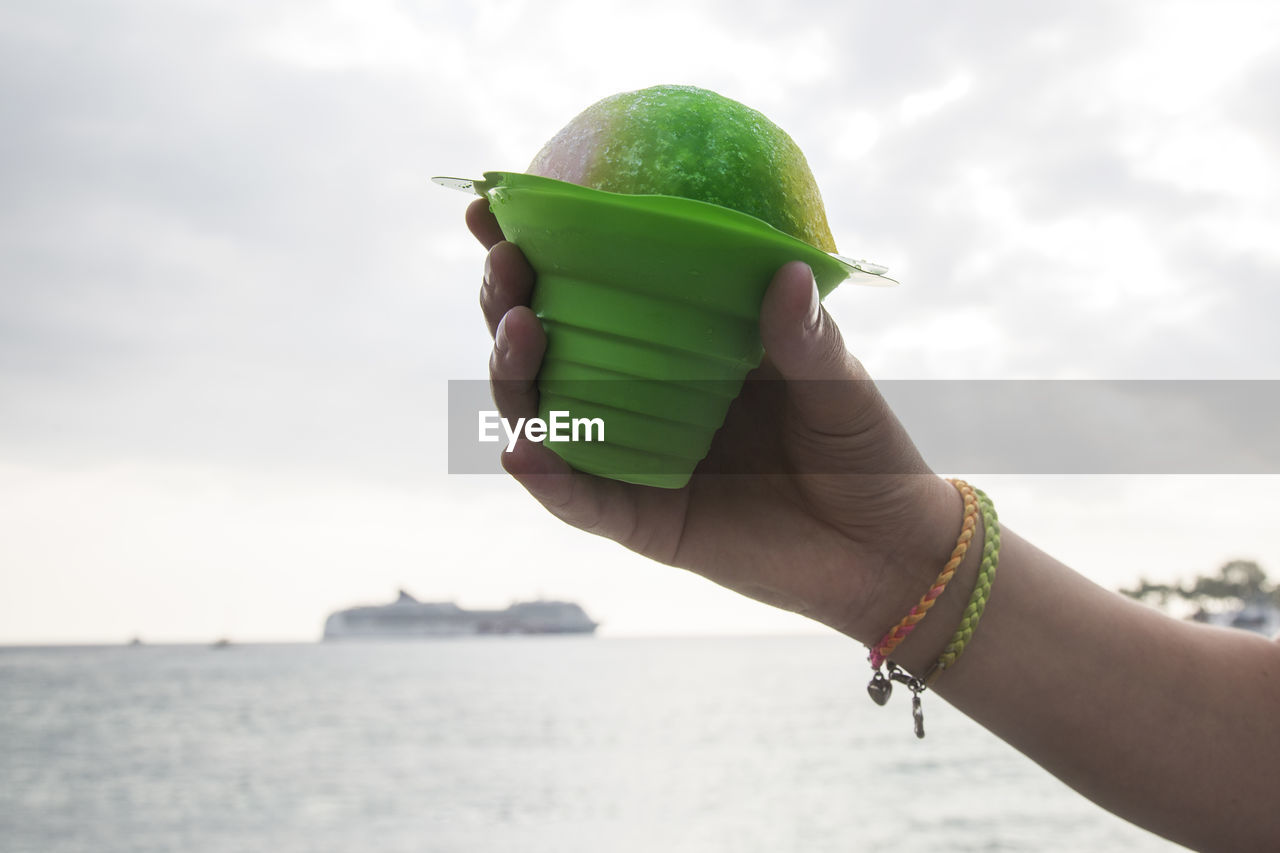 hand, holding, human hand, sky, food, healthy eating, one person, food and drink, green color, human body part, focus on foreground, day, nature, real people, lifestyles, cloud - sky, unrecognizable person, wellbeing, fruit, outdoors, finger