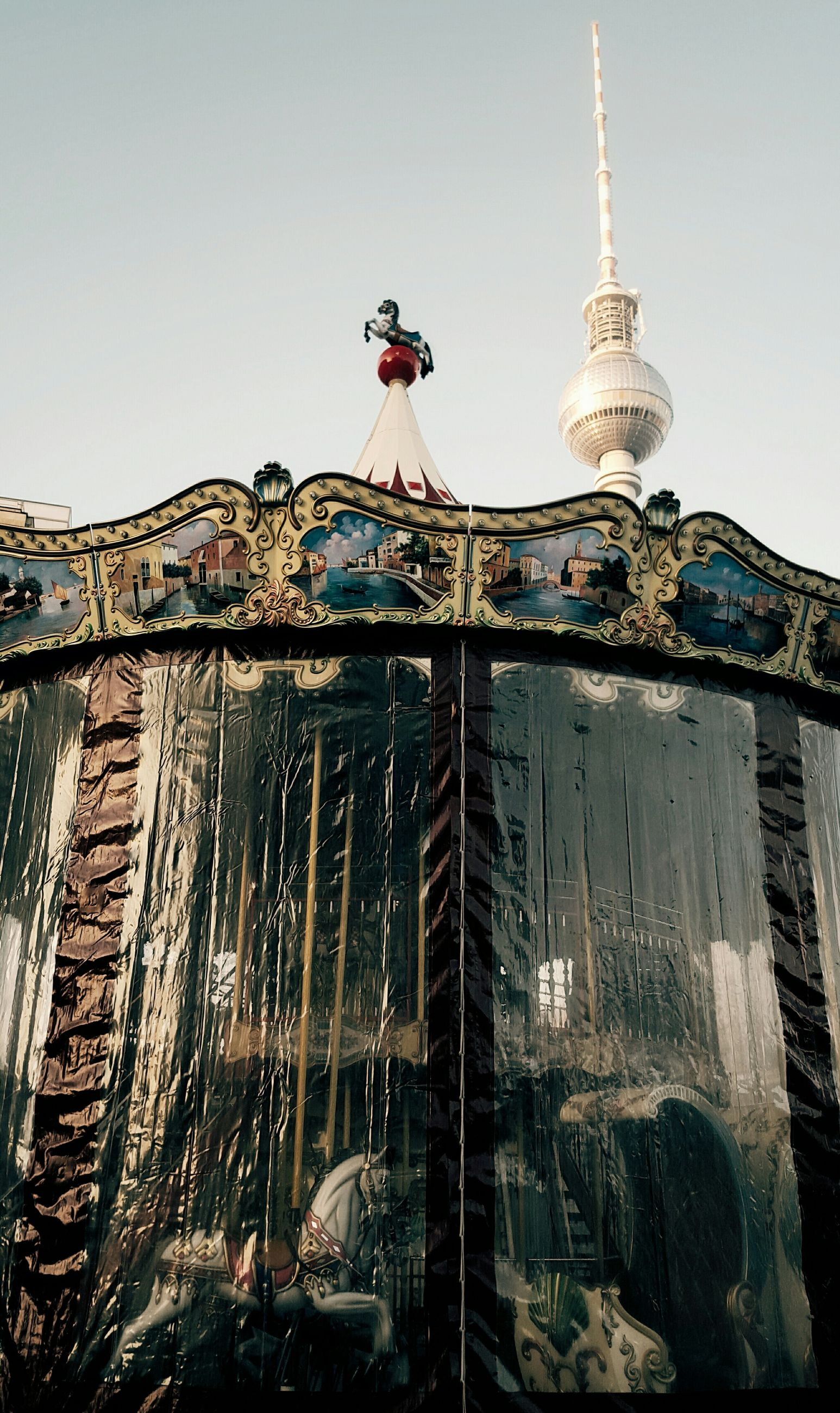 Low angle view of carousel and fernsehturm against sky