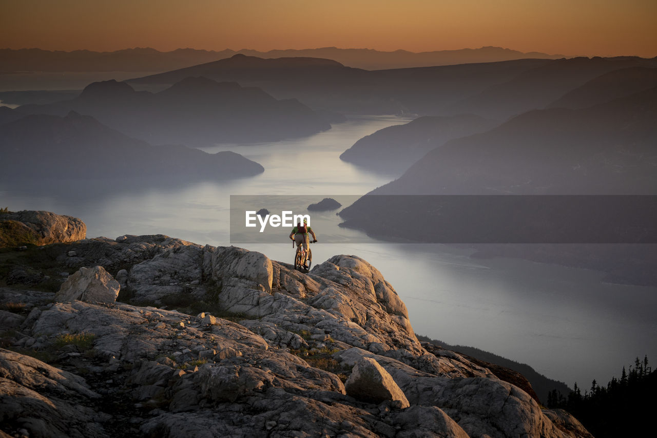 Man on rock by mountain against sky during sunset