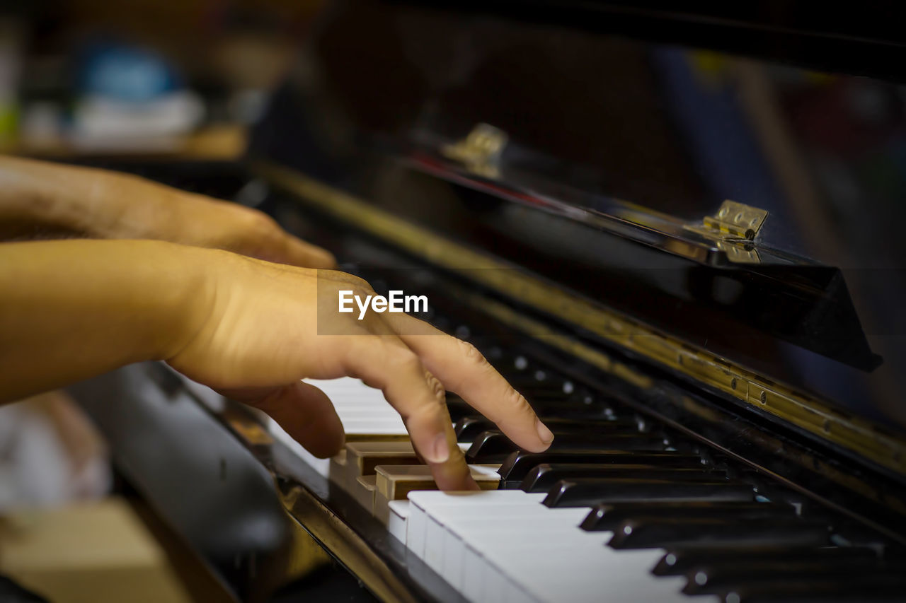 MIDSECTION OF PERSON PLAYING PIANO AT MUSIC CONCERT