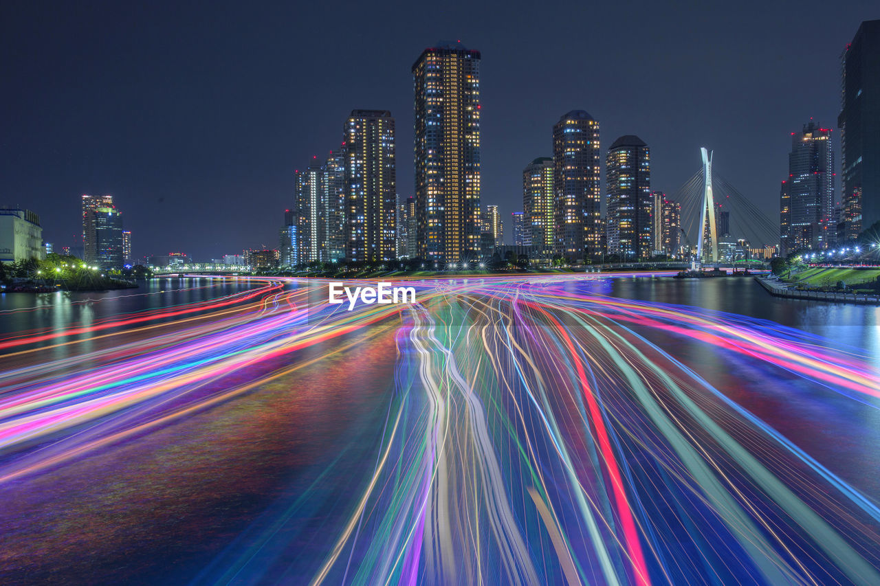 LIGHT TRAILS ON ROAD AMIDST ILLUMINATED BUILDINGS AT NIGHT