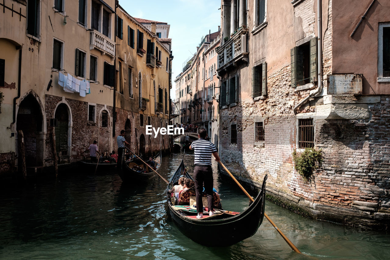 Rear View Of Gondolier In Gondola At Canal Amidst Old Buildings