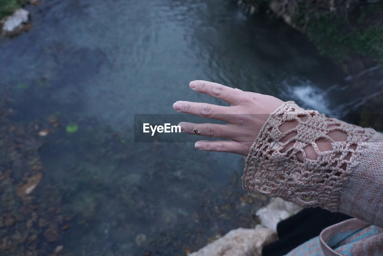 Close-up Of Hand Of Woman On Railing Of Bridge