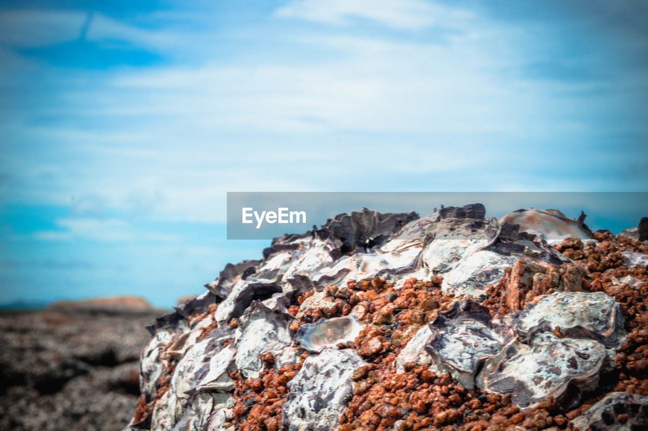 rock, sky, nature, solid, rock - object, cloud - sky, day, focus on foreground, no people, textured, beauty in nature, tranquility, land, close-up, scenics - nature, tranquil scene, sea, outdoors, rock formation, blue