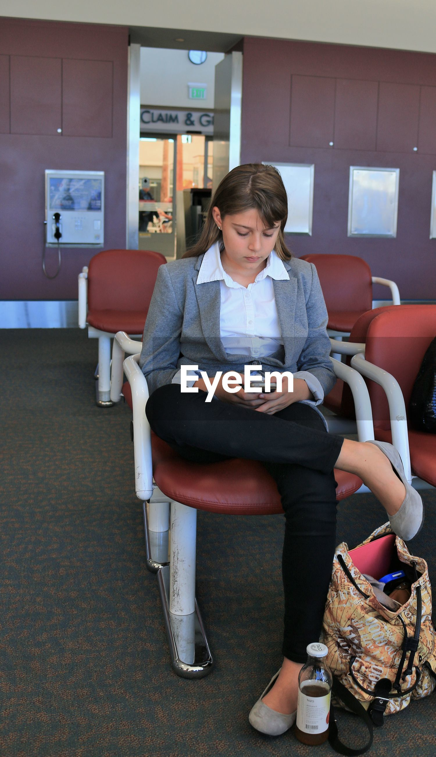 Woman using smart phone while sitting on chair at airport