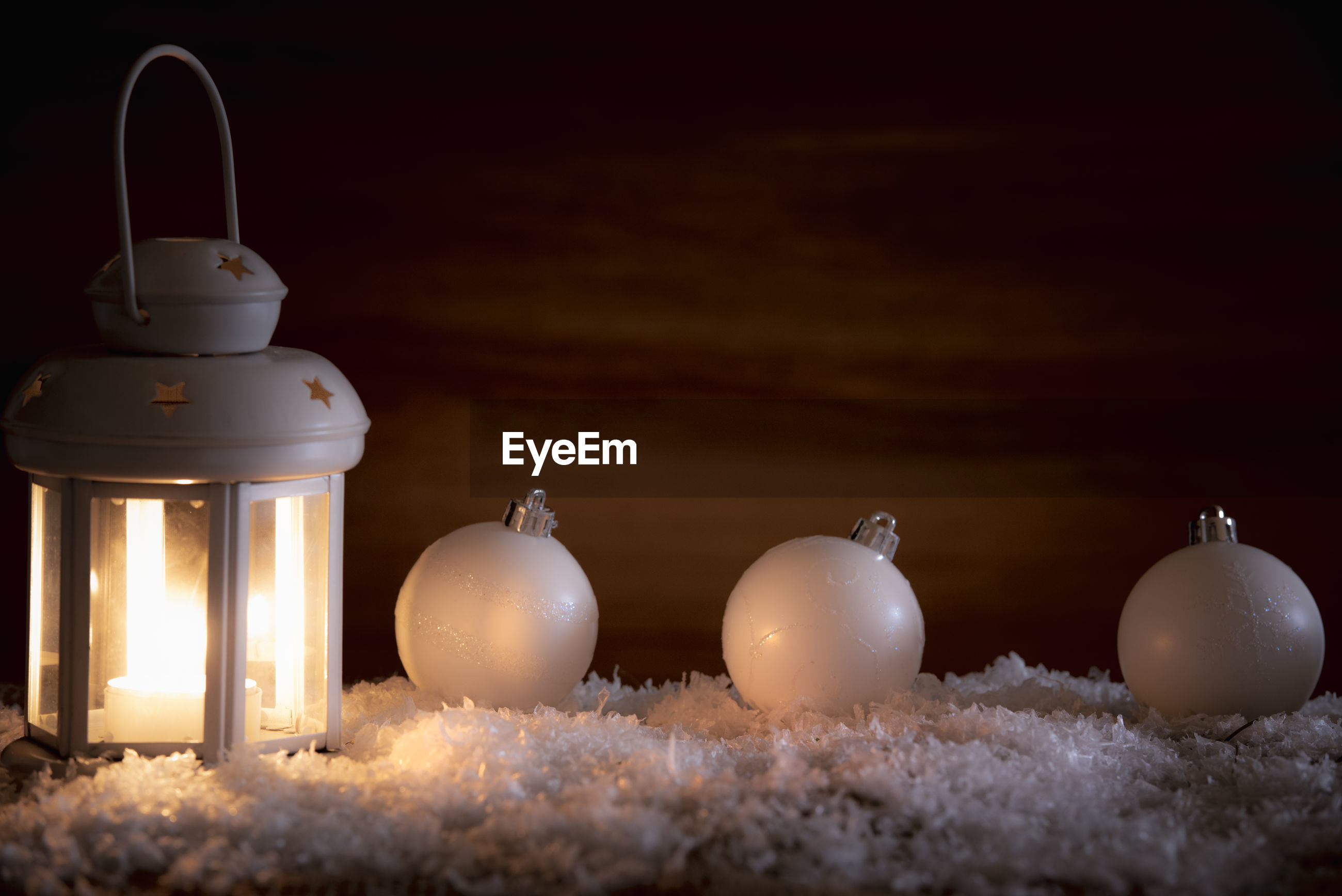 Close-up of baubles and candle on fake snow