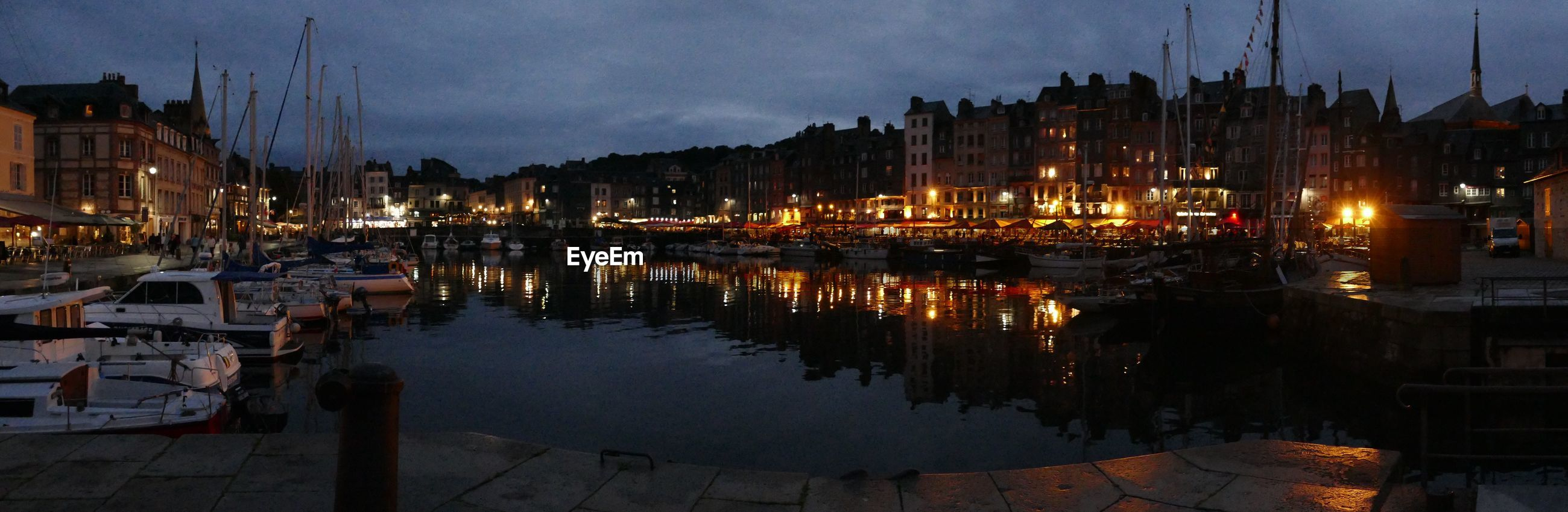 Panoramic view of illuminated port of honfleur against sky at night
