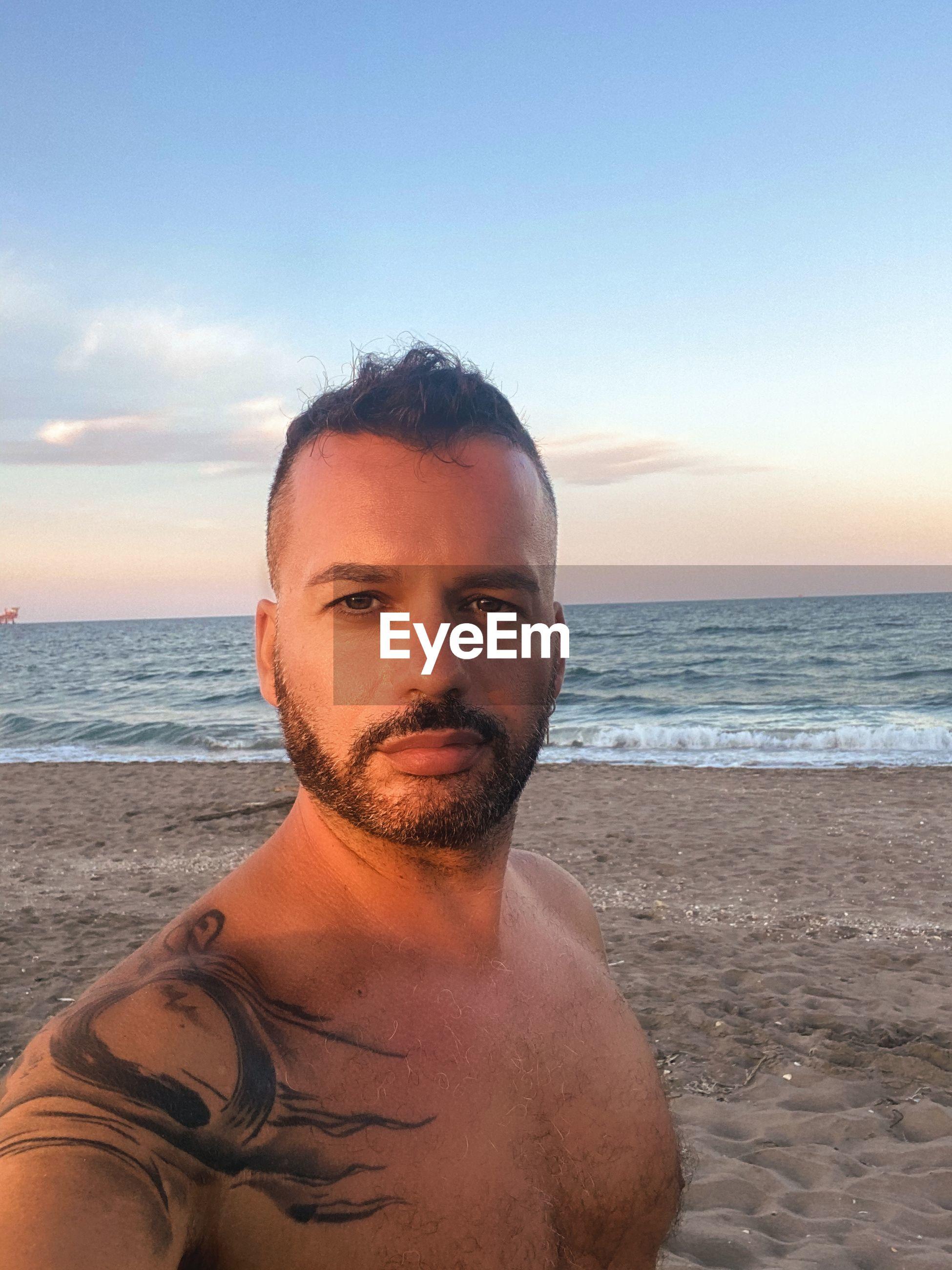 PORTRAIT OF MAN ON BEACH